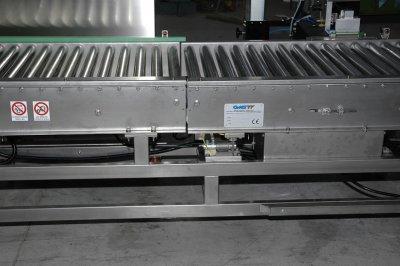 Trasportatore a rulli in acciaio INOX con sistema di pesatura in linea.